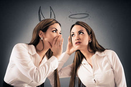 Mädchen mit Teufel Hörner spricht mit einem Mädchen wie ein Engel mit einem Halo