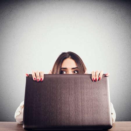 secretly: Woman hidden behind the computer screen peeks secretly Stock Photo