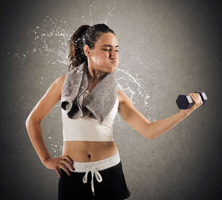 jaded: Woman raises a dumbbell weight sweating so much