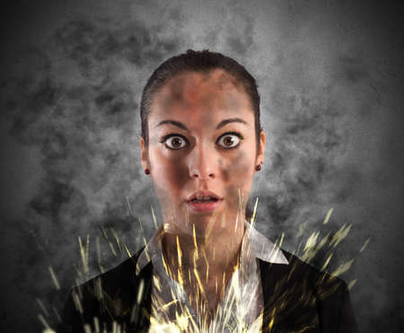 hazard: Woman with shocked expression smoke and sparks Stock Photo