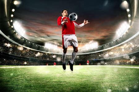 Piłkarz sparować piłkę na polu stadionu Zdjęcie Seryjne