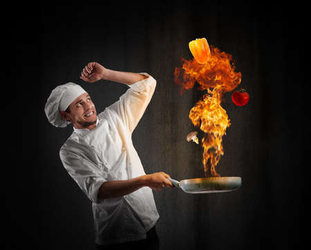 Cook chef with a big explosion in kitchen Foto de archivo