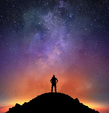 hombre cayendo: De excursión en una montaña observar un cielo brillante lleno de estrellas Foto de archivo