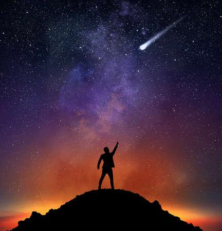 kosmos: Geschäftsmann auf einem Berg zeigen einen fallenden Stern
