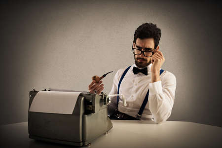 novelist: Man with glasses and pipe write with a typewriter Stock Photo