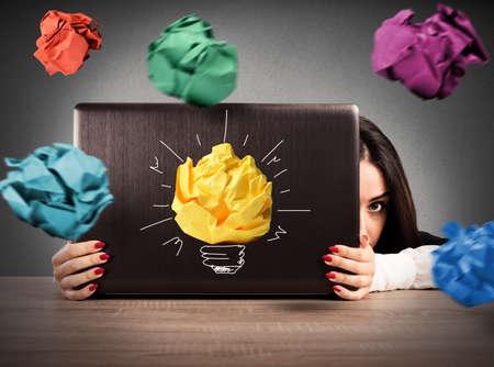 Zakenvrouw is beschermd achter het computerscherm van papieren ballen Stockfoto