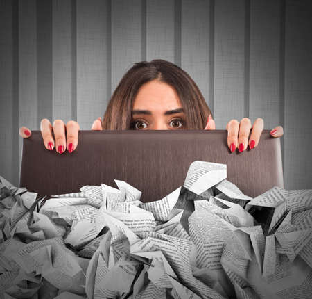stress woman: Businesswoman hidden behind the laptop screen submerged by the sheets Stock Photo