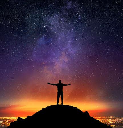 excitación: El hombre de negocios se regocija en una montaña con el fondo de cielo estrellado