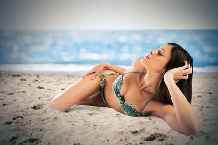sunbath: Woman in bikini lying on the shoreline