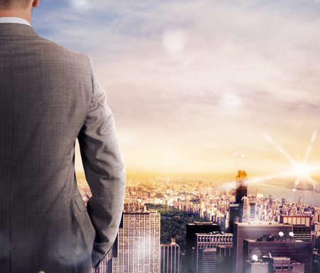 Businessman looks at the landscape of the city