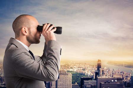 lejos: Hombre de negocios mira el paisaje de la ciudad con los prismáticos