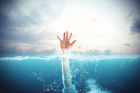 drowning: Businessman drowning in the sea and asks for help Stock Photo