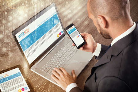 Businessman sitting at desk working with laptop tablet and cellphone