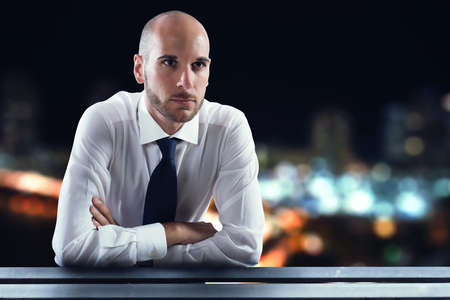 Businessman looks at the city from the window