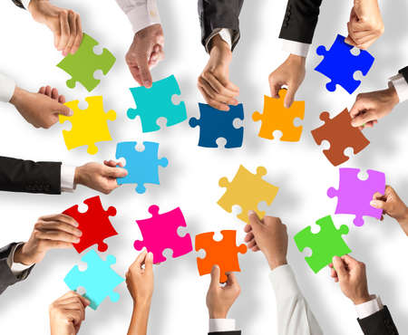 merging together: Business people join the colorful puzzle pieces. Concept of teamwork and integration Stock Photo