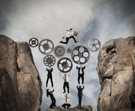 Business people support a gear mechanism for passing a man in the mountains Archivio Fotografico