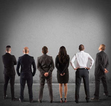 Business team kijken naar de grijze lege muur Stockfoto - 62101485