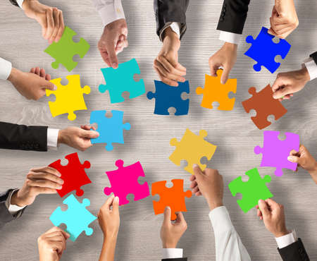 merging together: Business people join the colorful puzzle pieces