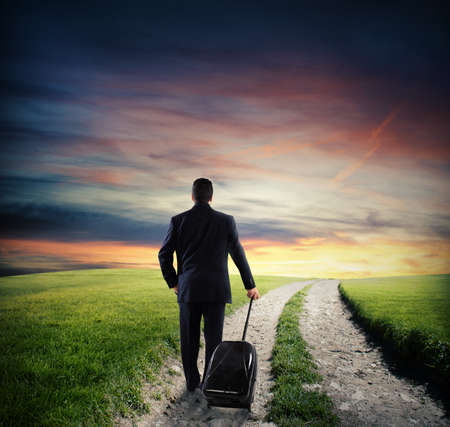 globetrotter: Businessman with luggage walk on road in the countryside with green grass at sunset Stock Photo