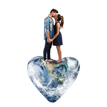 Lovely couple kissing on a heart-shaped world