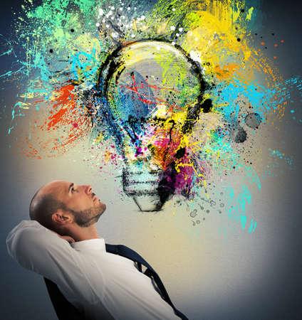 ビジネスマンの描かれた電球を見て椅子に座っているし、新しい創造的なアイデアを考えています。
