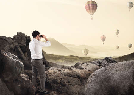 Businessman leaning on a rock watching hot-air balloons in the sky with binoculars