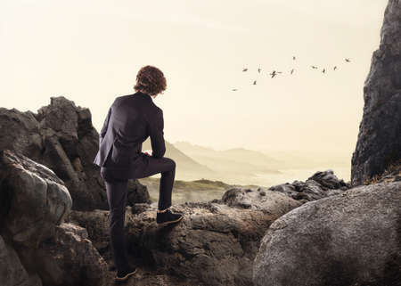 opportunity discovery: Businessman leaning on a rock watching the horizon Stock Photo