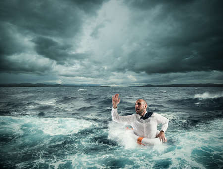 Man with lifesaver for help in a stormy sea