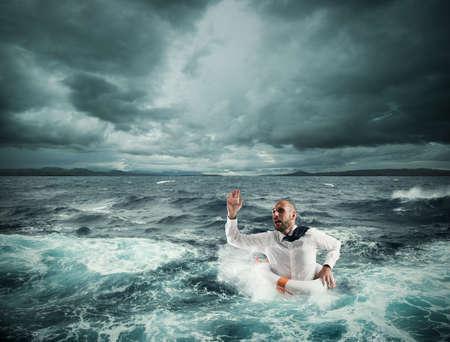 Hombre con salvavidas para ayuda en un mar tempestuoso Foto de archivo - 63506589