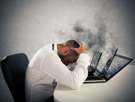 exhausted: Businessman with worried expression with computers in smoke