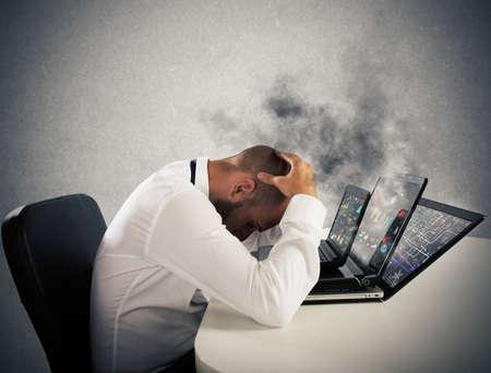 Homme d'affaires avec l'expression inquiète avec des ordinateurs dans la fumée