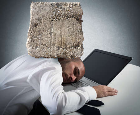 office desk: Businessman sleeping on a computer keyboard with a big rock over his head