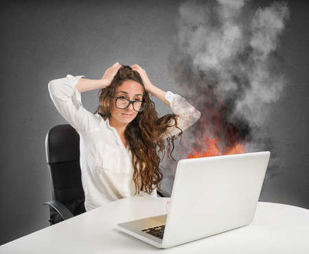 Businesswoman with stressed expression looks at the laptop on fire 스톡 콘텐츠