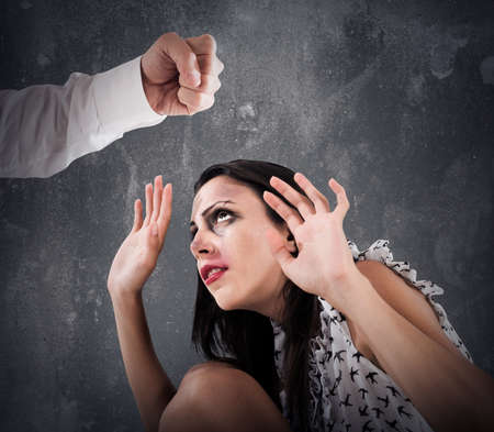 submissive: Scared woman with bruises from a man fist Stock Photo