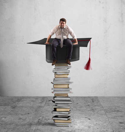 Businessman sitting on a pile of books with graduation hat Stock Photo