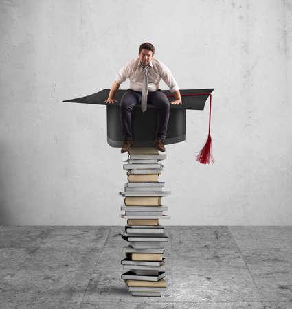 cognicion: De negocios sentado en una pila de libros con el sombrero de la graduación Foto de archivo