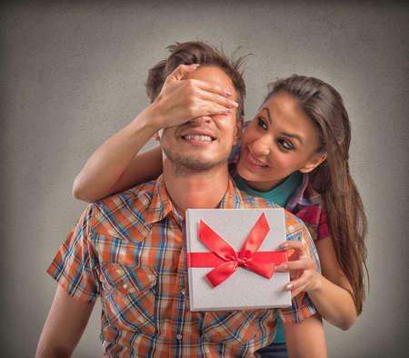Fille couvre les yeux garçon tout donne à lui une boîte-cadeau Banque d'images