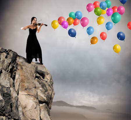 Violinist plays on a mountain with colorful balloons flying