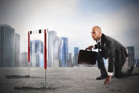 El hombre de negocios listo para carrera se ve un obstáculo en el camino