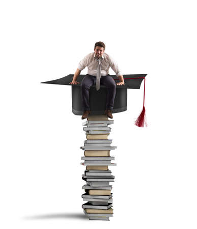 Businessman sitting on a pile of books with graduation hat Banco de Imagens