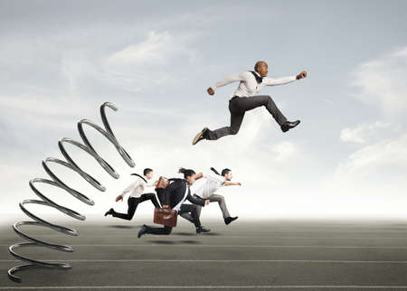 disadvantage: Businessman jumping on a spring during a race with opponents Stock Photo