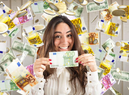 Happy businesswoman shows a 100 euro banknote with rain of money background