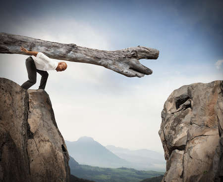 impediment: Man carries a trunk in a crevice between two mountains Stock Photo