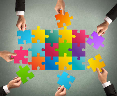 oneness: Businessmen working together to build a colored puzzle