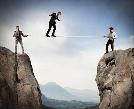 Zakenmensen die een touw houden terwijl een man gebalanceerd loopt Stockfoto