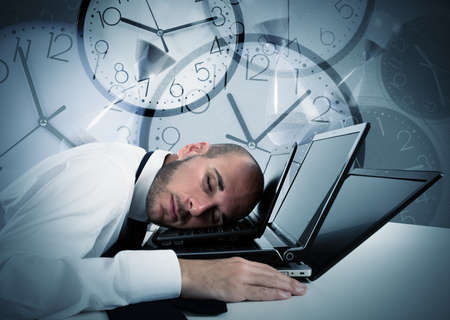 working on computer: Businessman sleeping on laptop and background with watches Stock Photo
