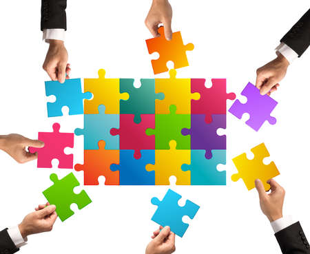 merging together: Businessmen working together to build a colored puzzle