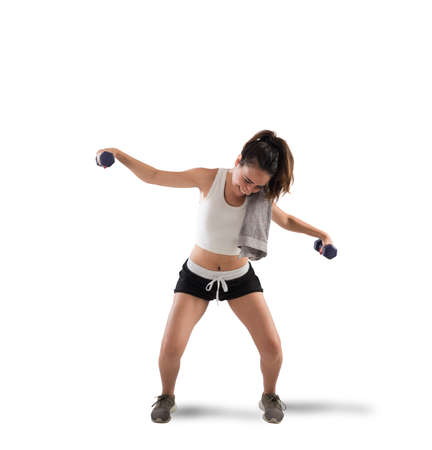 levantar pesas: Awkward girl trying to lift weights during workout Foto de archivo
