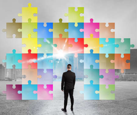 merging together: Man looks a puzzle built with colored pieces Stock Photo