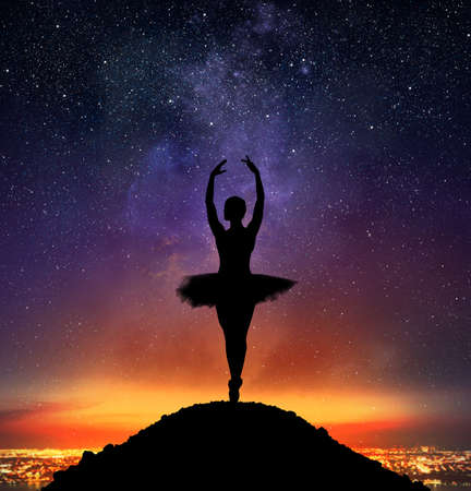 atmosphere: Dancer in a pose of classical dance on pointe on a mountain Stock Photo
